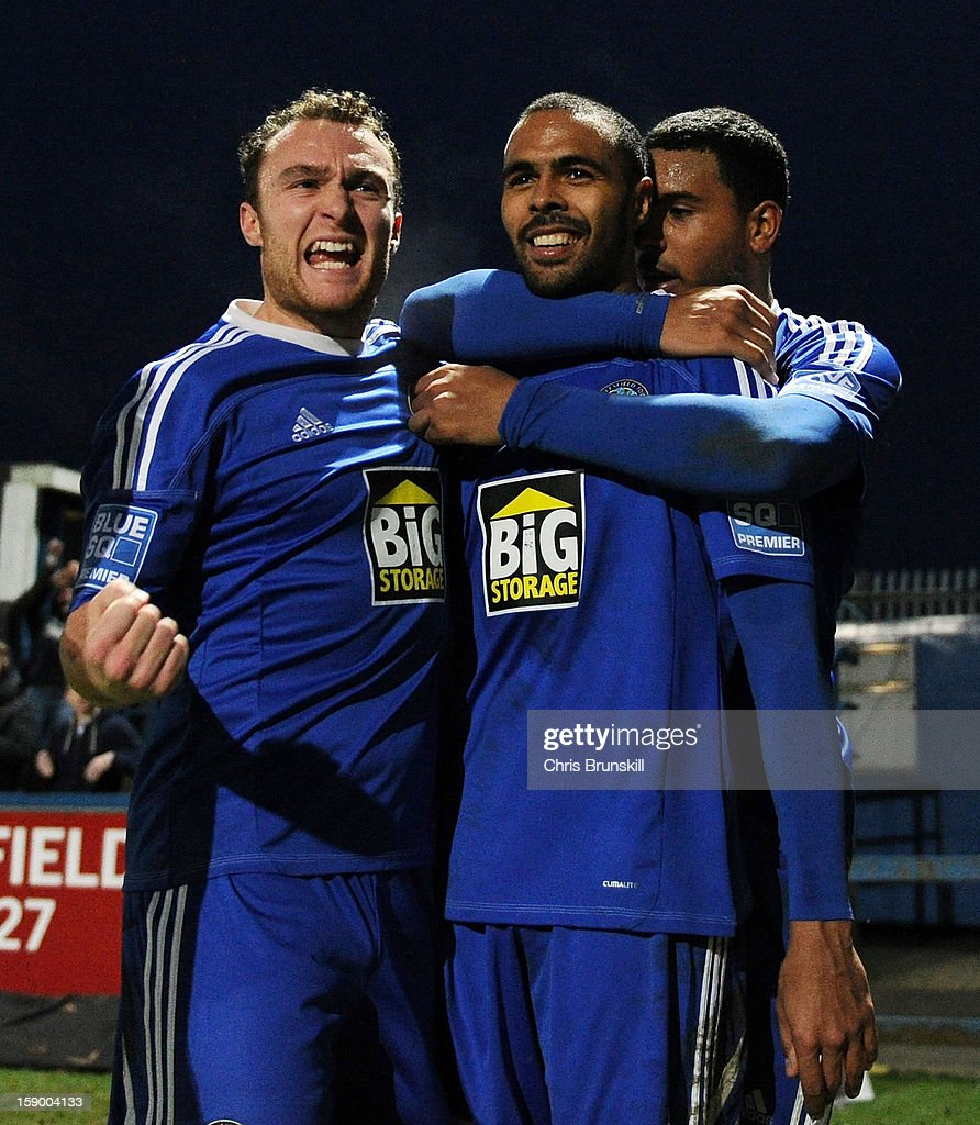 Matthew Barnes-Homer (C) of Macclesfield Town is congratulated by team-mates Peter Winn (L) and Keiran Murtagh after scoring the equaliser during the FA Cup with Budweiser Third Round match between Macclesfield Town and Cardiff City at Moss Rose Ground on January 5, 2013 in Macclesfield, England.