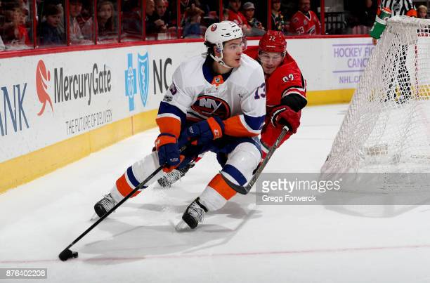 Matthew Barzal of the New York Islanders controls the puck away from Brett Pesce of the Carolina Hurricanes during an NHL game on November 19 2017 at...