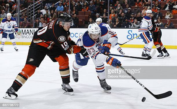Matthew Benning of the Edmonton Oilers battles for the puck against Corey Perry of the Anaheim Ducks during the game on January 25 2017 at Honda...