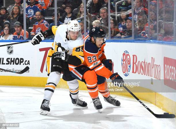 Matthew Benning of the Edmonton Oilers battles for the puck against Jake Guentzel of the Pittsburgh Penguins on November 1 2017 at Rogers Place in...