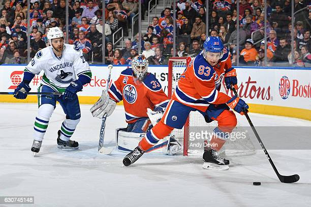 Matthew Benning of the Edmonton Oilers controls the puck away from Brandon Sutter of the Vancouver Canucks on December 31 2016 at Rogers Place in...