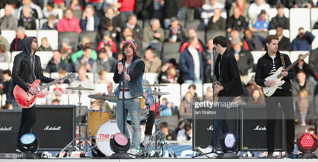 Matthew Bowman (C) of the Pigeon Detectives performs prior to kick off during the FA Cup Fifth Round match between MK Dons and Barnsley at StadiumMK on February 16, 2013 in Milton Keynes, England.