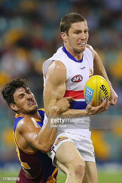 Matthew Boyd of the Bulldogs is tackled by Sam Mayes of the Lions during the round 22 AFL match between the Brisbane Lions and the Western Bulldogs...