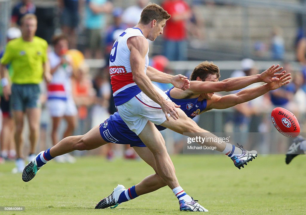 Matthew Boyd of the Bulldogs kicks the ball away from a diving Liam Picken of the Bulldogs during the Western Bulldogs AFL intra-club match at Whitten Oval on February 13, 2016 in Melbourne, Australia.