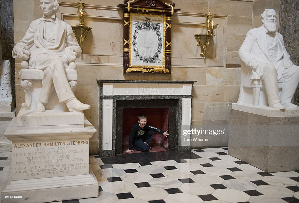 Matthew Cronin, 9, of Spokane, Wash., checks out a fireplace in the Capitol's Statuary Hall.