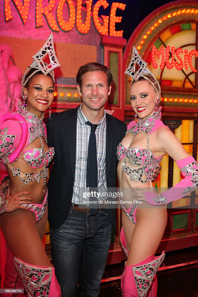 Matthew Davis poses backstage with the dancers of the Moulin Rouge after they have attended the show at Le Moulin Rouge on May 22, 2013 in Paris, France.