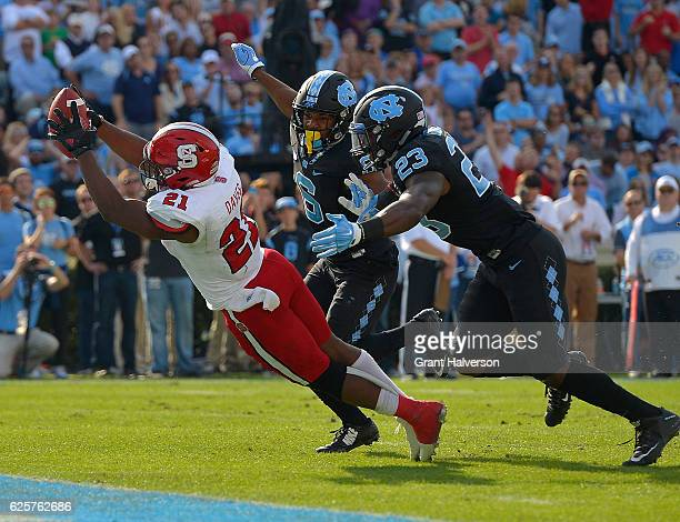 Matthew Dayes of the North Carolina State Wolfpack dives into the end zone as MJ Stewart and Cayson Collins of the North Carolina Tar Heels pursue...