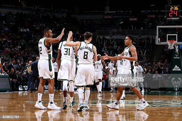 Matthew Dellavedova Jabari Parker and Malcolm Brogdon of the Milwaukee Bucks high five each other during the game against the Atlanta Hawks on...