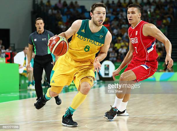 Matthew Dellavedova of Australia moves the ball past Bogdan Bogdanovic of Serbia during the Men's Semifinal match on Day 14 of the Rio 2016 Olympic...