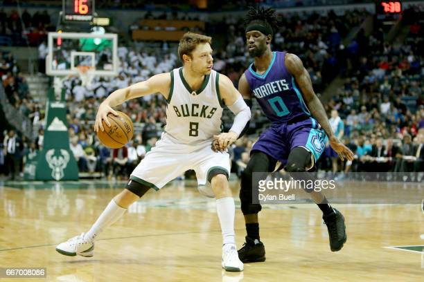 Matthew Dellavedova of the Milwaukee Bucks dribbles the ball while being guarded by Briante Weber of the Charlotte Hornets in the second quarter at...