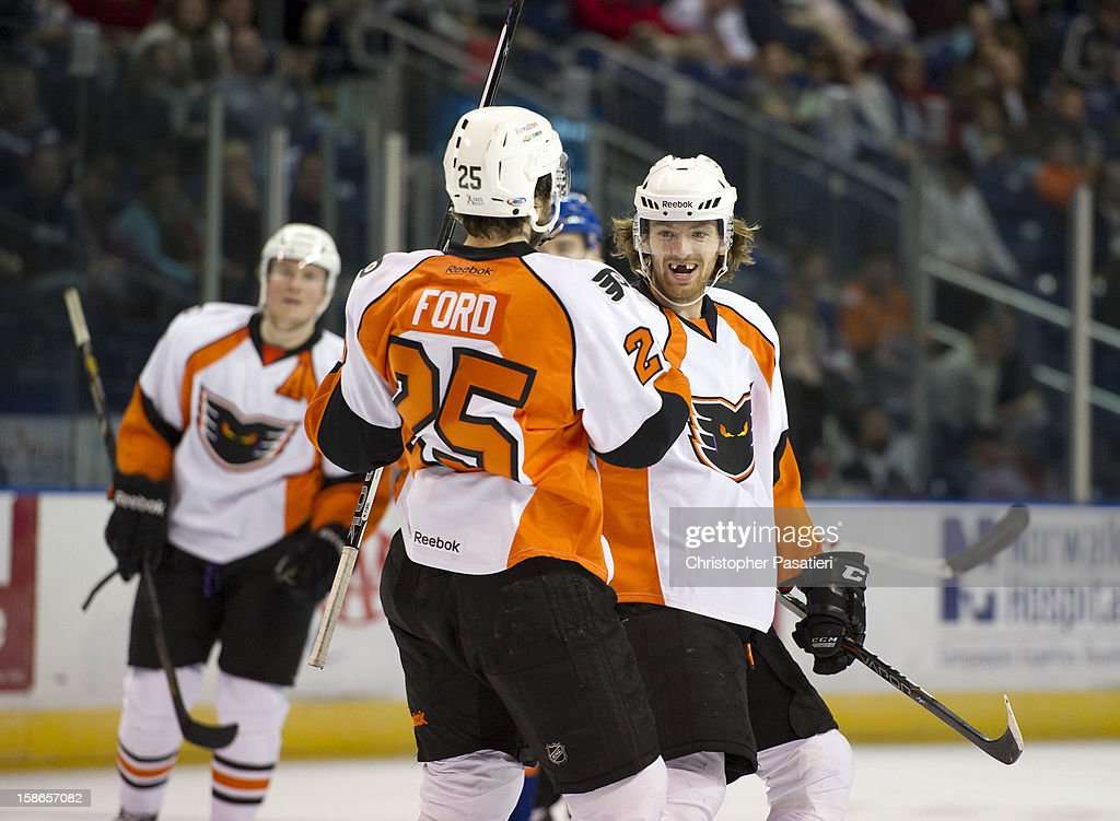 Matthew Ford #25 of the Adirondack Phantoms is congratulated by Sean Couturier #14 after scoring a goal against the Bridgeport Sound Tigers during an American Hockey League game on December 22, 2012 at the Webster Bank Arena at Harbor Yard in Bridgeport, Connecticut.