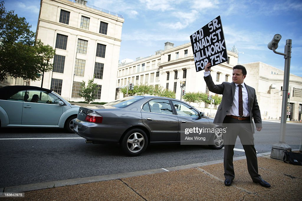 Matthew Giarmo of Alexandria, Virginia, who lost his contract job with the Department of Health and Human Services in 2012, holds up a sign seeking a job with a lower salary than he would normally ask on a street corner October 8, 2013 in Washington, DC. With his wife furloughed from her job at the Smithsonian Institution due to the U.S. government shutdown, Giarmo, who has a Ph.D. in social-personality psychology, said he had no choice but to stand on the street to find work.