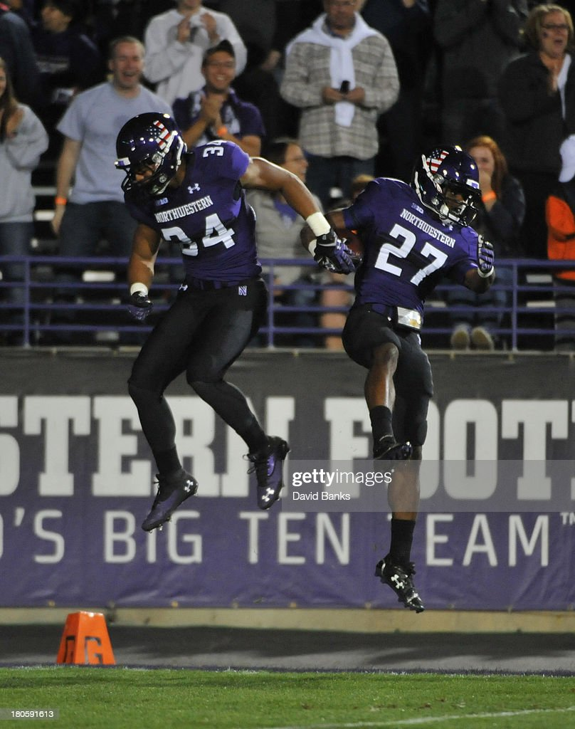 Matthew Harris #27 of the Northwestern Wildcats celebrates with Warren Long # #34 after a good kickoff return against the Western Michigan Broncos during the first quarter on September 14, 2013 at Ryan Field in Evanston, Illinois.