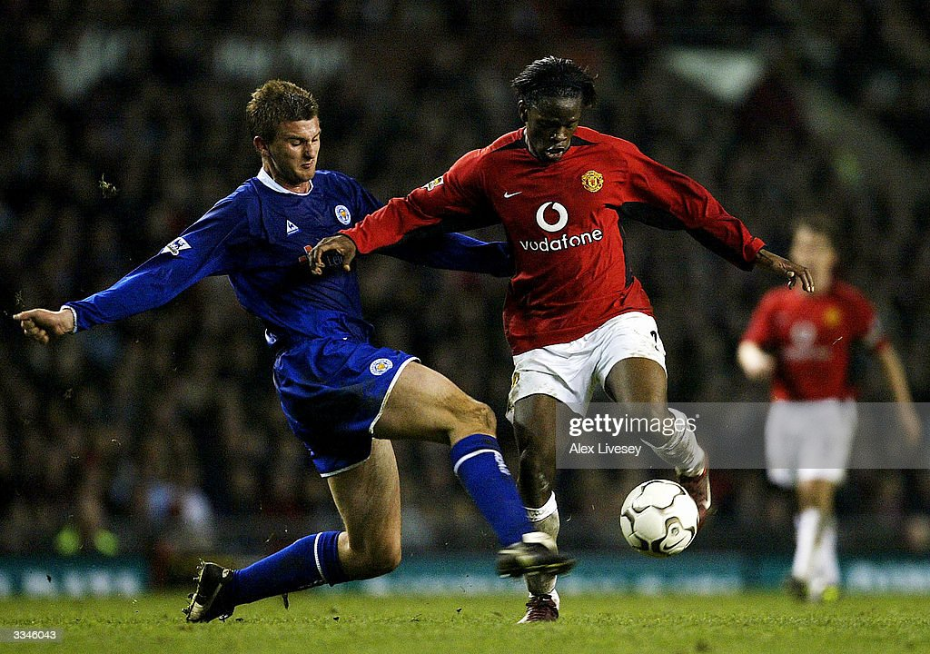 Matthew Heath of Leicester City tackles Louis Saha of Manchester United during the FA Barclaycard Premiership match between Manchester United and Leicester City at Old Trafford on April 13, 2004 in Manchester, England.