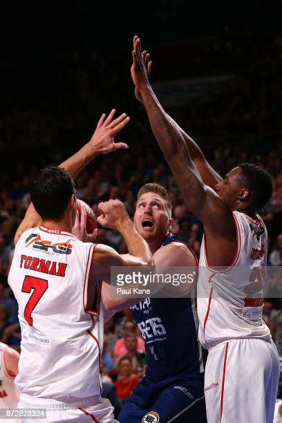 Matthew Hodgson of the 36ers goes to the basket against Oscar Foreman and Delvon Johnson of the Hawks during the round six NBL match between the...