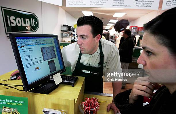 Matthew Johnston General Manager of a branch of iSold It researches prices with a customer dropping off goods December 13 2004 in Huntington New York...