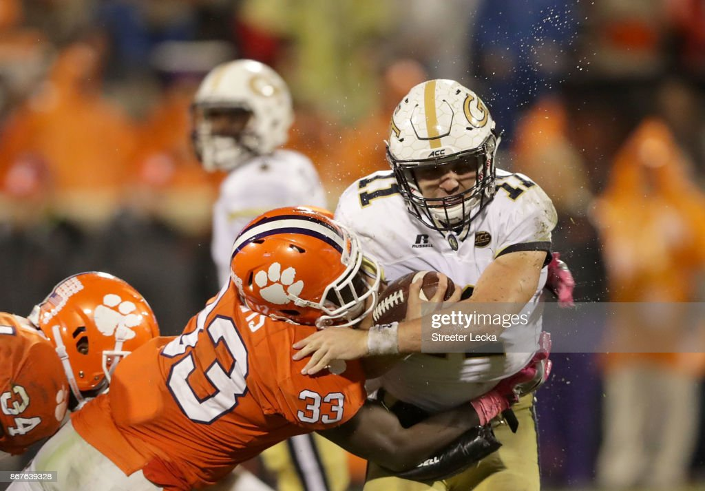 Matthew Jordan #11 of the Georgia Tech Yellow Jackets is hit by J.D. Davis #33 of the Clemson Tigers during their game at Memorial Stadium on October 28, 2017 in Clemson, South Carolina.