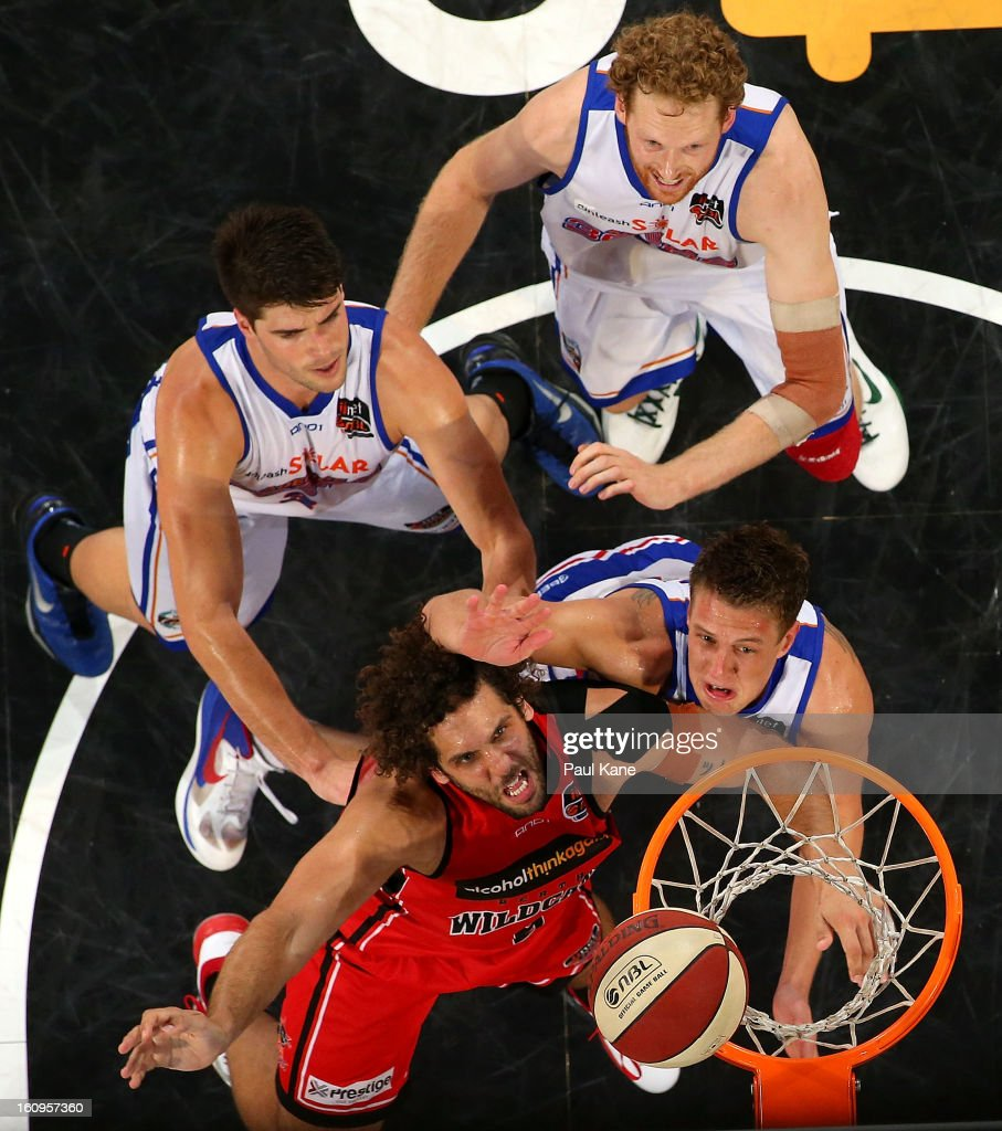 Matthew Knight of the Wildcats contests a rebound against Daniel Johnson Stephen Weigh and Luke Schenscher of the 36ers during the round 18 NBL match...