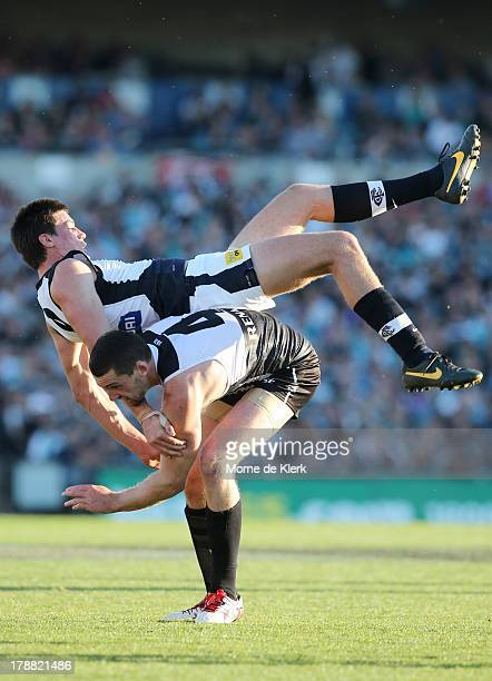 Matthew Kreuzer of the Blues falls over Brent Renouf of the Power during the round 23 AFL match between Port Adelaide Power and the Carlton Blues at...