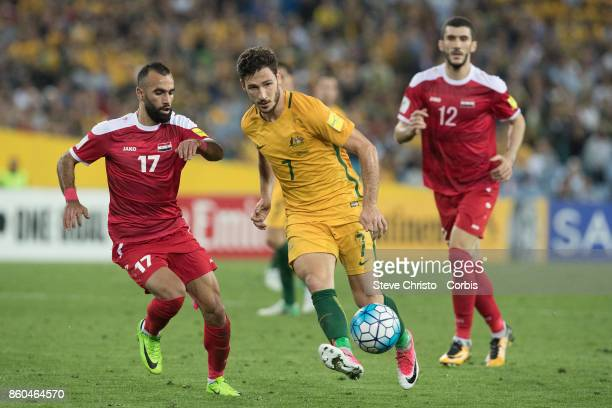 Matthew Leckie of Australia beats Osama Omari of Syria during the 2018 FIFA World Cup Asian Playoff match between the Australian Socceroos and Syria...