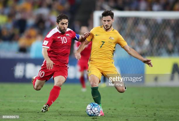 Matthew Leckie of Australia is challenged by Feras Al Khatib of Syria during the 2018 FIFA World Cup Asian Playoff match between the Australian...