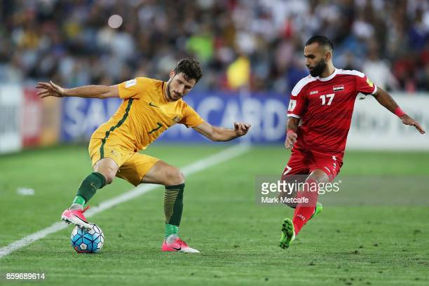 Matthew Leckie of Australia takes on Osama Omari of Syria during the 2018 FIFA World Cup Asian Playoff match between the Australian Socceroos and...