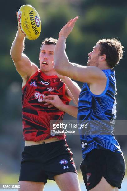 Matthew Leuenberger of the Bombers taps the ball away from Tom Bellchambers during an Essendon Bombers AFL training session at True Value Centre on...
