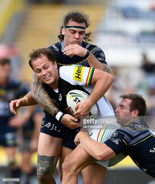 Matthew Moylan of the Panthers is tackled by Michael Morgan and Ethan Lowe of the Cowboys during the round 16 NRL match between the North Queensland...