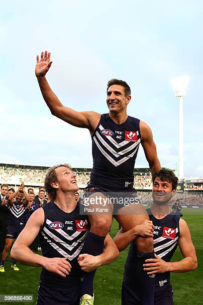Matthew Pavlich of the Dockers is chaired from the ground by David Mundy and Alex Silvagni after playing his 353rd and final game during the round 23...