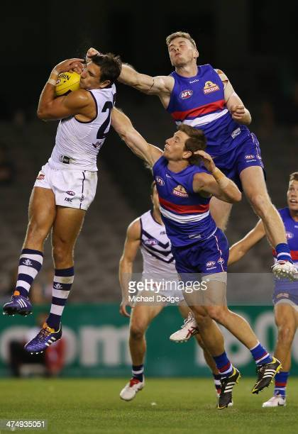 Matthew Pavlich of the Dockers marks the ball against Jordan Roughead and Dale Morris of the Bulldogs marks the ball during the round three AFL NAB...