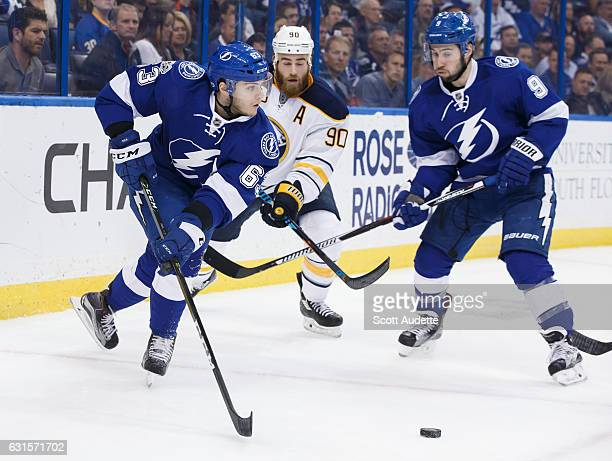 Matthew Peca and Tyler Johnson of the Tampa Bay Lightning skate against Ryan O'Reilly of the Buffalo Sabres during the first period at Amalie Arena...