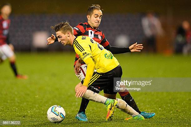Matthew Ridenton of the Phoenix is tackled by Steven Lustica of the Wanderers during the FFA Cup Round of 32 match between the Western Sydney...