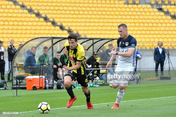 Matthew Ridenton of the Wellington Phoenix makes a run down the sideline with Besart Berisha of Melbourne Victory marking him during the round nine...