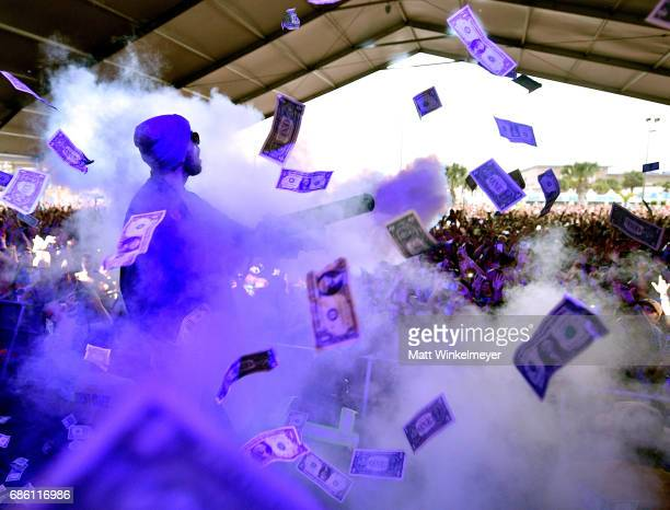 Matthew Russell of Cheat Codes shoots dollar bills into the audience at The Boom Boom Tent during 2017 Hangout Music Festival on May 20 2017 in Gulf...
