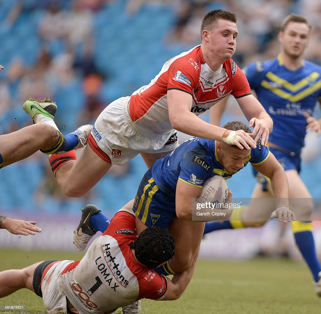 Matthew Russell of Warrington Wolves is tackled by Jonny Lomax and Joe Greenwood of St Helens during the Super League match between Warrington Wolves and St Helens at Etihad Stadium on May 18, 2014 in Manchester, England.