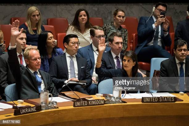 Matthew Rycroft United Kingdom ambassador to the United Nations and Nikki Haley United States ambassador to the United Nations raise their hands as...