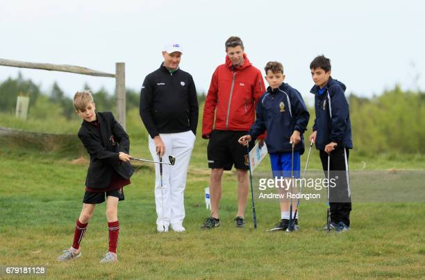 Matthew Sands is watched by professional Sam Brazel of Australia and schoolchildren during a Golf Foundation GolfSixes Academy event at prior to the...