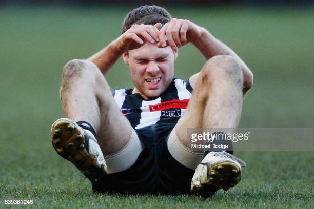 Matthew Scharenberg of the Magpies reacts after a collision during the round 22 AFL match between the Collingwood Magpies and the Geelong Cats at...