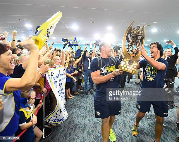 Matthew Scott and Johnathan Thurston of the Cowboys hold the NRL trophy aloft after arriving back at the Townsville airport before heading out to the...