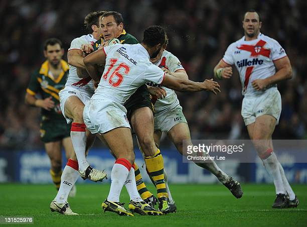 Matthew Scott of Australia is tackled by Ben Westwood Jamie Jones Buchanan and James Roy of England during the Four Nations match between England and...