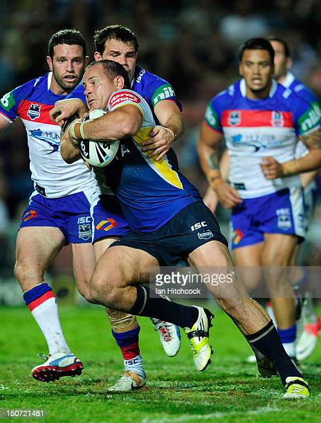 Matthew Scott of the Cowboys is tackled by Adam Cuthbertson of the Knights during the round 25 NRL match between the North Queensland Cowboys and the...
