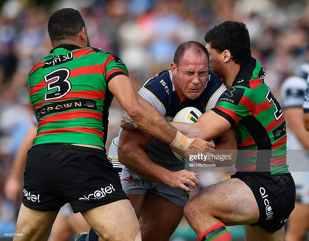 Matthew Scott of the Cowboys is tackled by Greg Inglis and Kyle Turner of the Rabbitohs during the round 17 NRL match between the South Sydney Rabbitohs and the North Queensland Cowboys at Barlow Park on July 3, 2016 in Cairns, Australia.