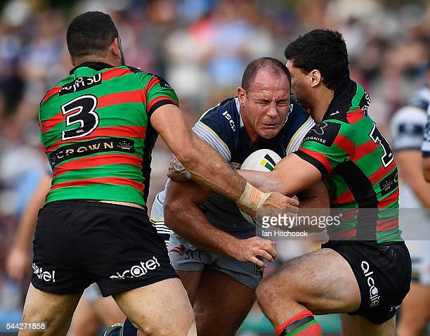 Matthew Scott of the Cowboys is tackled by Greg Inglis and Kyle Turner of the Rabbitohs during the round 17 NRL match between the South Sydney...