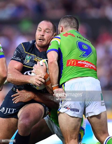 Matthew Scott of the Cowboys is tackled by Josh Hodgson of the Raiders during the round one NRL match between the North Queensland Cowboys and the...