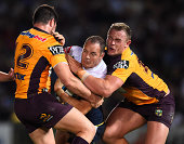 Matthew Scott of the Cowboys is tackled by Matt Gillett and Martin Kennedy of the Broncos during the NRL 1st Elimination Final match between the...