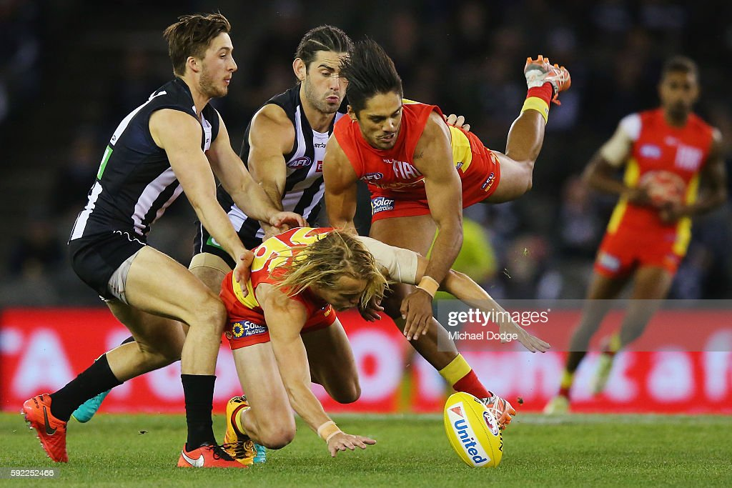 Matthew Shaw of the Suns and Aaron Hall R compete for the ball against Tom Phillips of the Magpies during the round 22 AFL match between the...