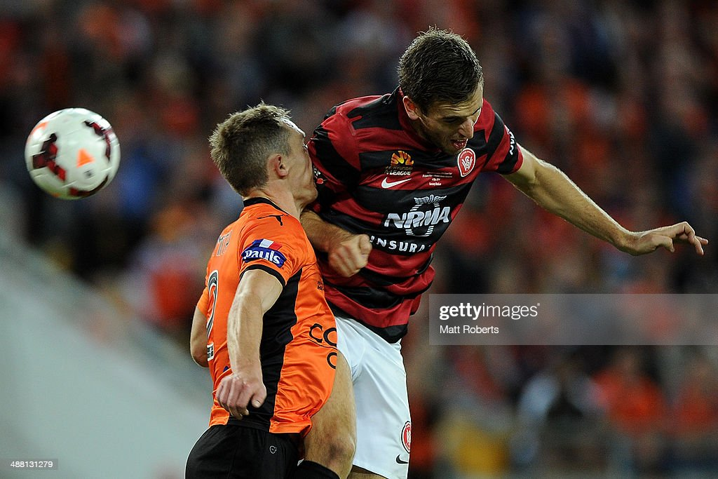 Matthew Smith of the Roar competes for the ball with Matthew Spiranovic of the Wanderers during the 2014 A-League Grand Final match between the Brisbane Roar and the Western Sydney Wanderers at Suncorp Stadium on May 4, 2014 in Brisbane, Australia.