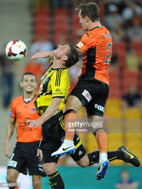 Matthew Smith of the Roar heads the ball over Benjamin Sigmund of the Phoenix during the round 16 ALeague match between Brisbane Roar and the...
