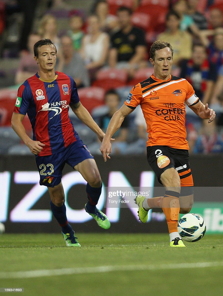 Matthew Smith (R) of the Roar passes the ball in front of Ryan Griffiths of the Jets during the round 16 A-League match between the Newcastle Jets and the Brisbane Roar at Hunter Stadium on January 12, 2013 in Newcastle, Australia.