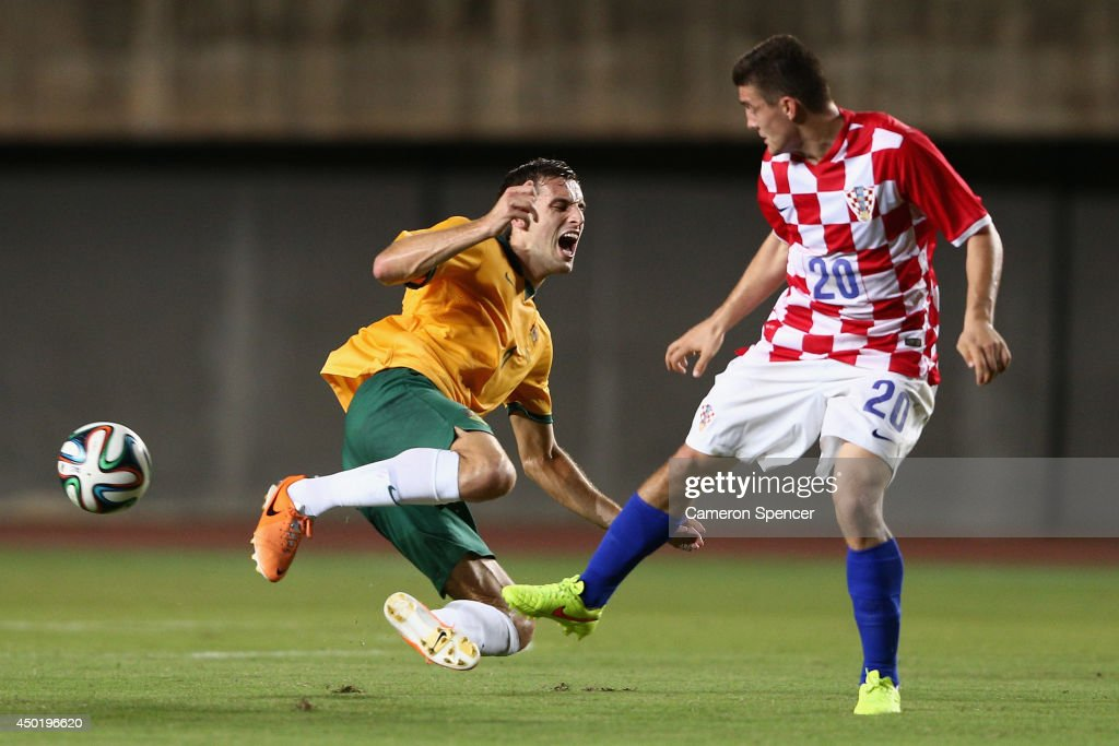Matthew Spiranovic of the Socceroos is tackled by Mateo Kovacic of Croatia during the International Friendly match between Croatia and the Australian Socceroos at Pituacu Stadium on June 6, 2014 in Salvador, Brazil.